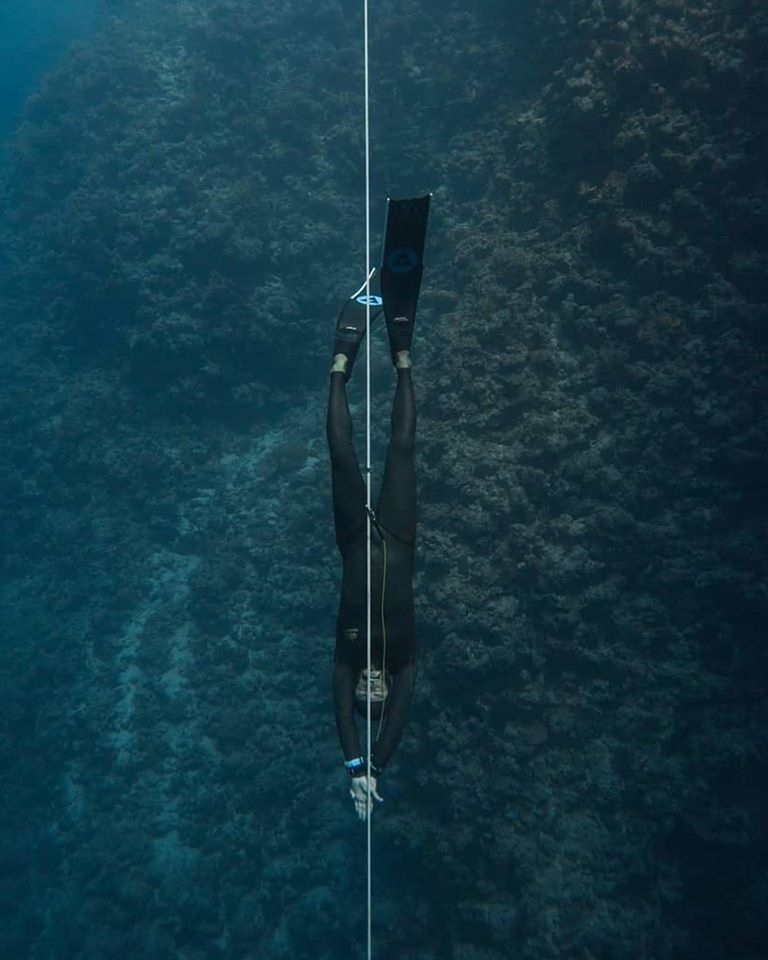 freediver in black wetsuit and alchemy v3 carbon fins underwater