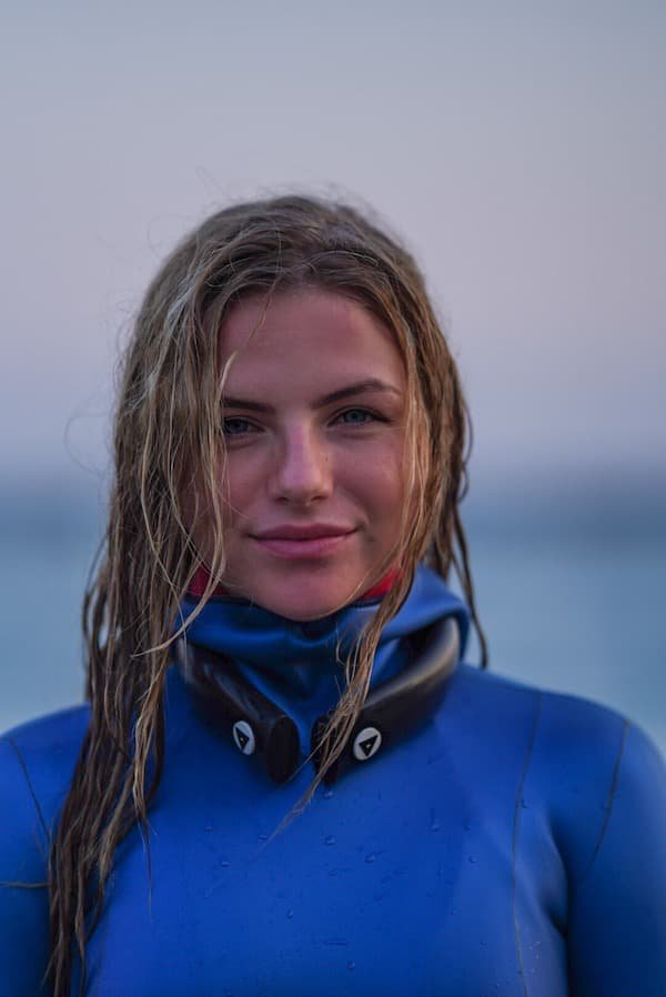 Blond woman in blue wetsuit smiling